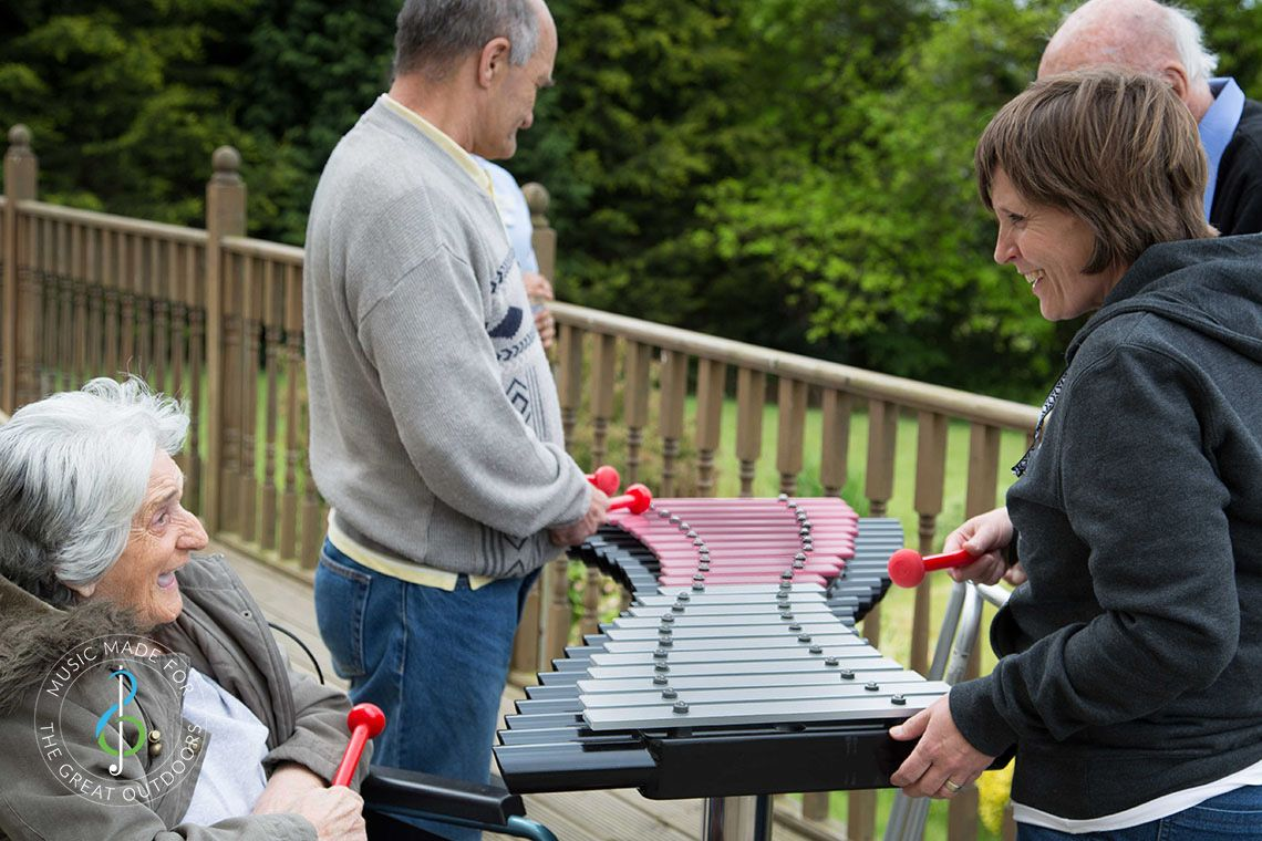 Elderly lady in a wheelchair laughing with her carer as they play on an outdoor xylophone in a care home garden
