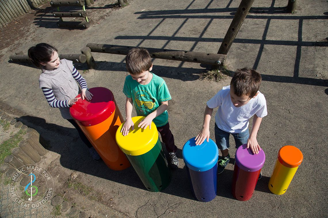 overhead shot of three children playing colourful outdoor drums in a playground