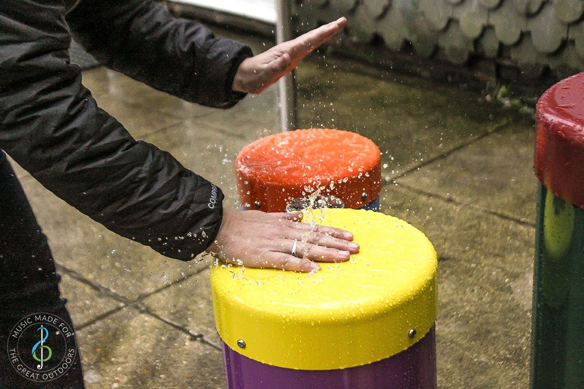 Pair of hands slapping down on bright coloured outdoor congas drums in the rain
