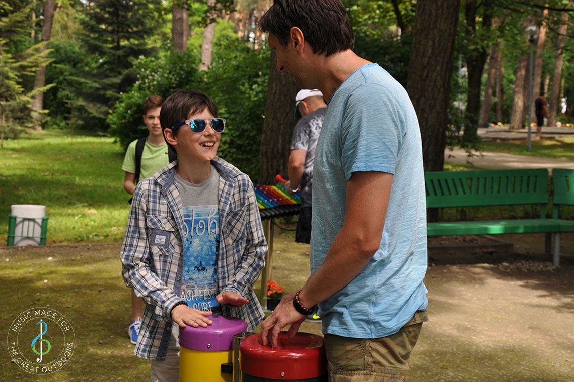 Teenage Boy wearing sunglasses with his father playing outdoor conga drums in playground with musical instruments