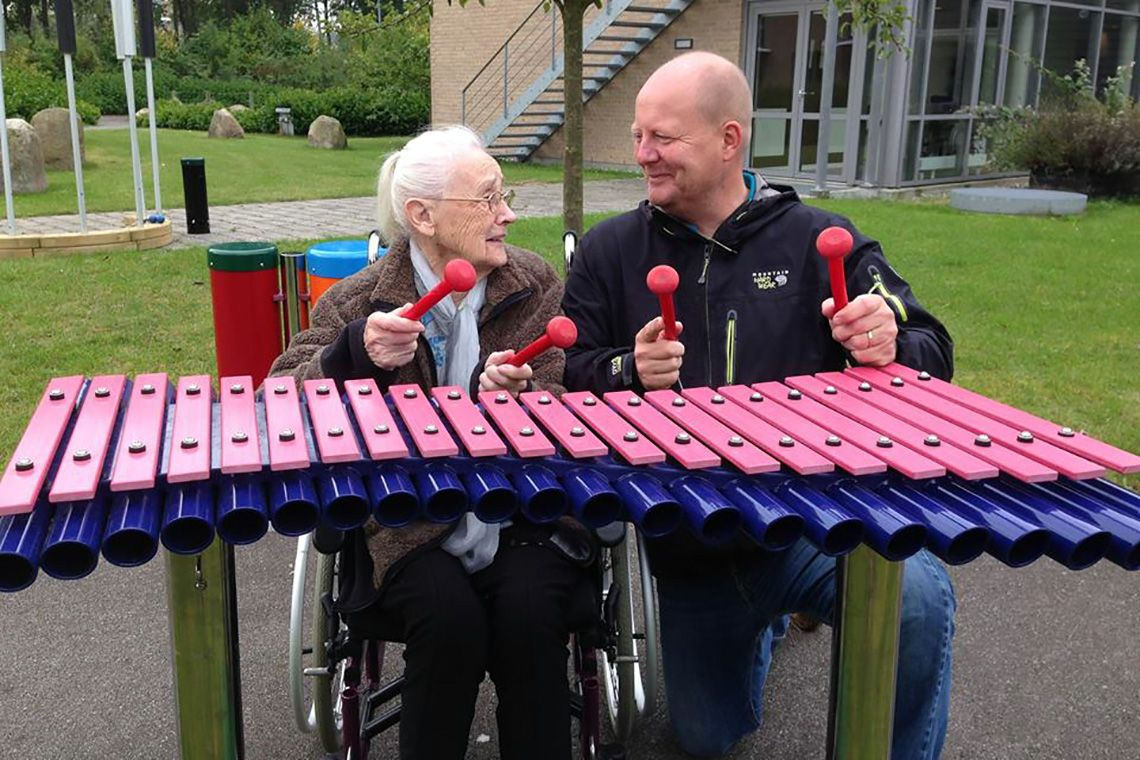 older lady and younger man playing an outdoor xylophone together in a care home garden