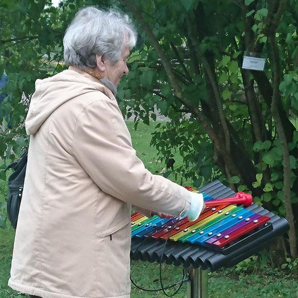 Older lady playing colourful xylophone in a park