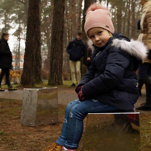 Little girl in bobble hat sat on a stainless steel cajon drum in a city park