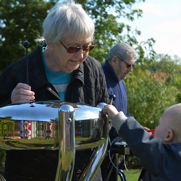 Older Lady and Small Child Playing Stainless Steel Tongue Drum Outdoors
