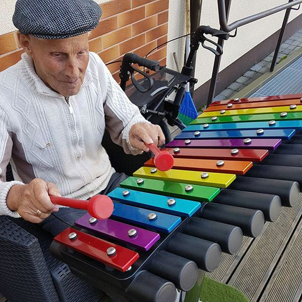 Elderley man sat playing a large colourful xylophone in a courtyard garden