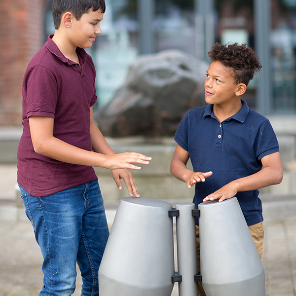 two young brothers are playing a pair of tumbardora steel drums with their hands in the street