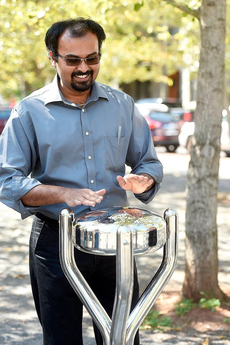 man in a park playing a large metal outdoor tongue drum