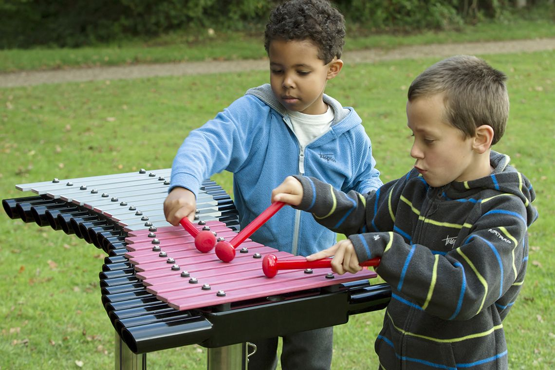 two little boys playing a large xylophone in a playground
