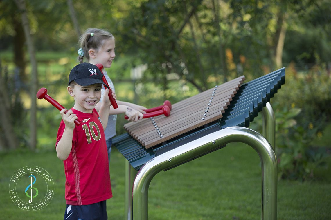 boy smiling and girl inbackground both playing large outdoor marimba xylophone in the park
