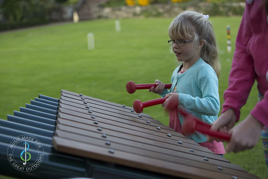 young girl wearing glasses playing on a large outdoor marimba xylophone in the park