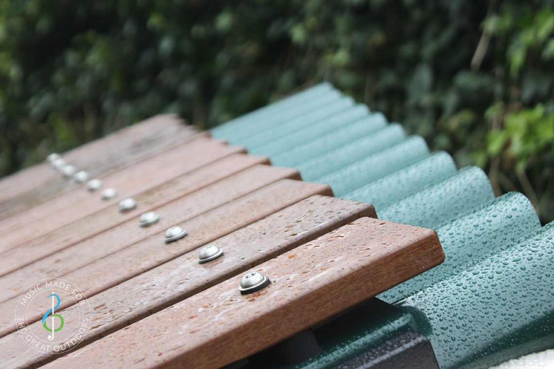 close up of wet timber notes of large outdoor xylophone