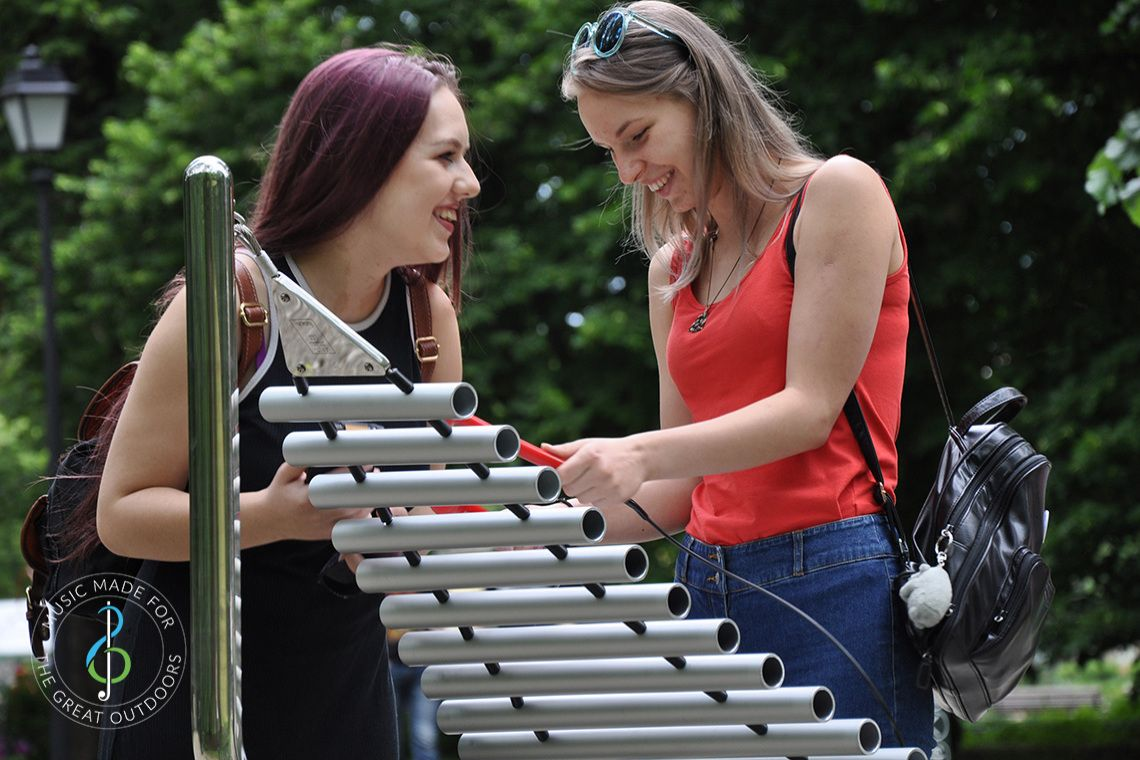 two young women laughing and playing a large outdoor musical instrument together in the park