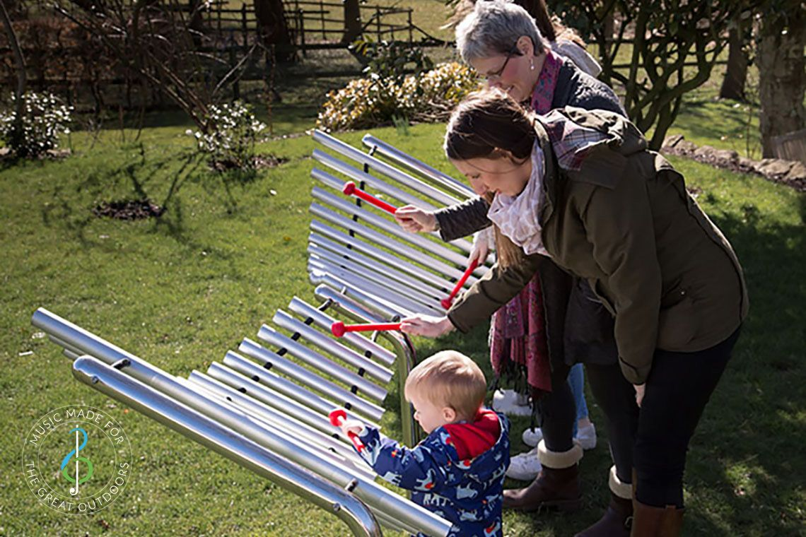 Family playing on large outdoor xylophone together in the park