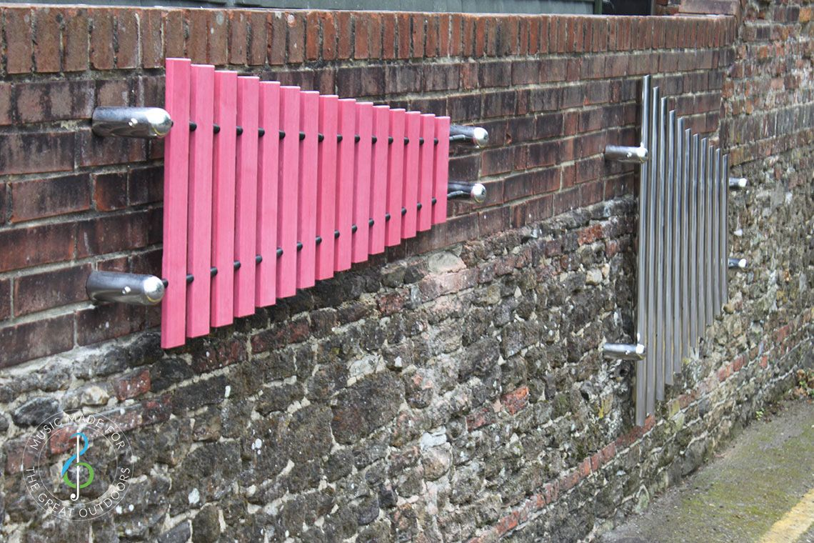 one large xylophone marimba with pink notes and one set of mirrored chimes both mounted on brick wall outdoors