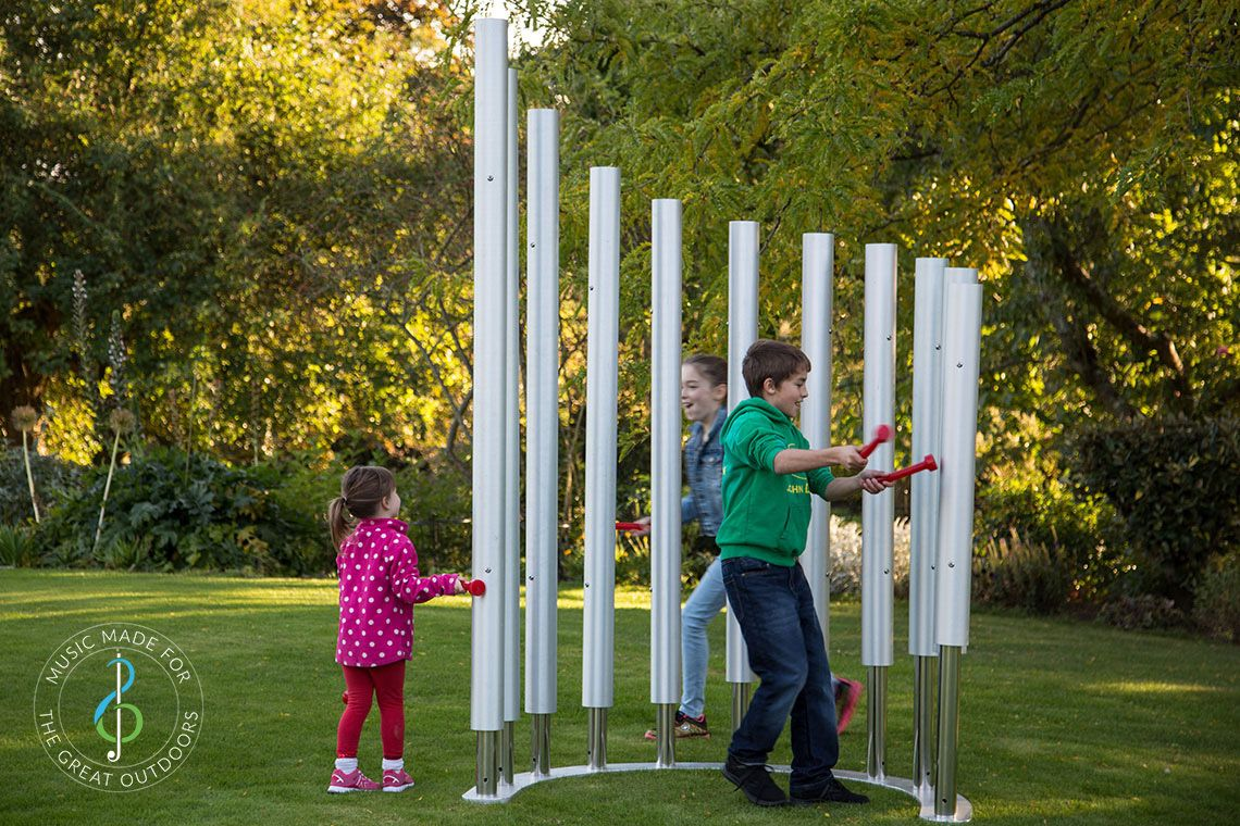 Two girls and one boy playing on 11 huge silver outdoor musical chimes set on grass