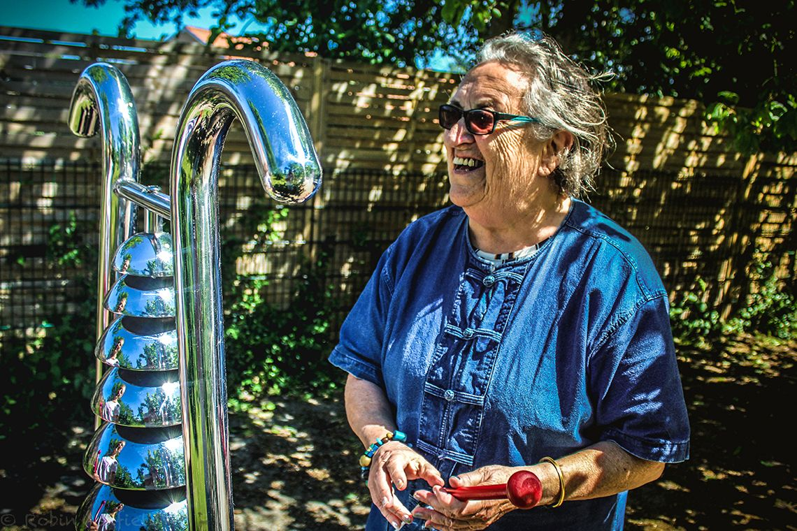 older lady laughing playing a large outdoor bell tree instrument