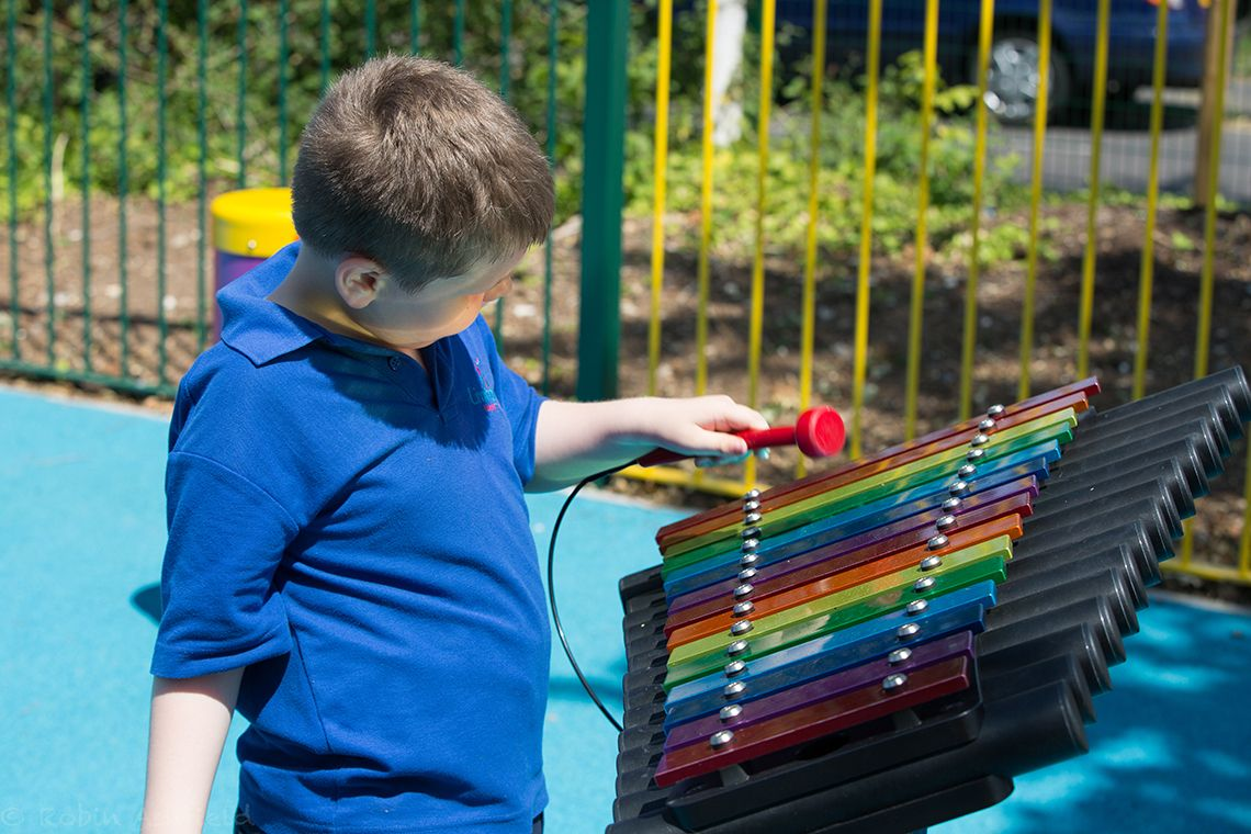 boys with special needs playing rainbow coloured chimes outdoors