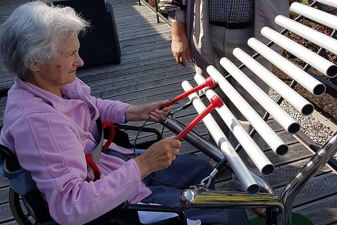 older lady in a wheelchair playing a large metallophone in a care home garden