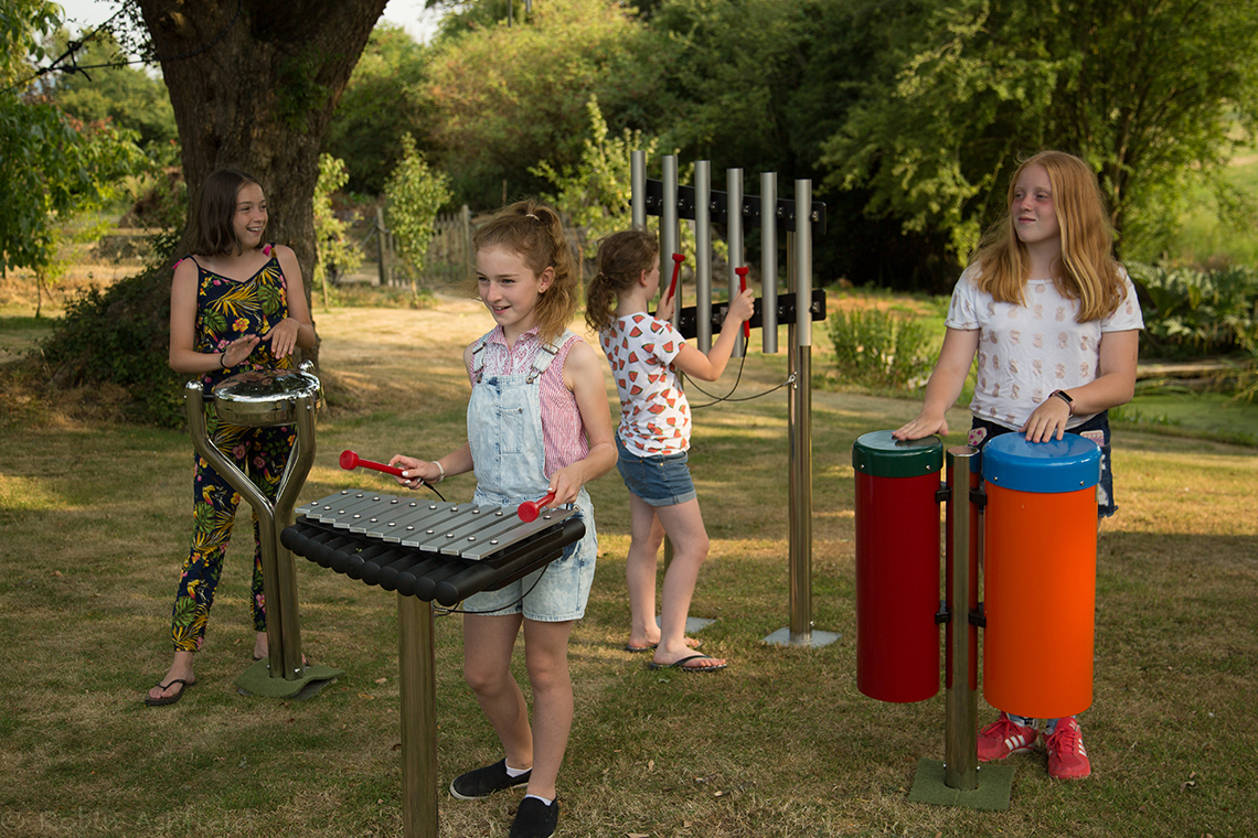 group of four children playing on an ensemble of outdoor musical instruments in a park